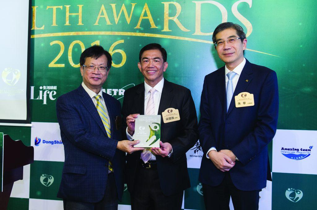 主禮嘉賓鄭耀棠及朱華先生向領袖人物獎得主美國輝瑞科研製藥香港區總經理梁國強先生(中)頒發獎座。