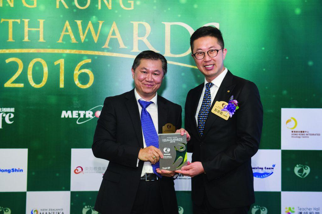 創健醫療執行董事方陽醫生(左)在著名外科整形醫生彭志宏手上接過獎座。