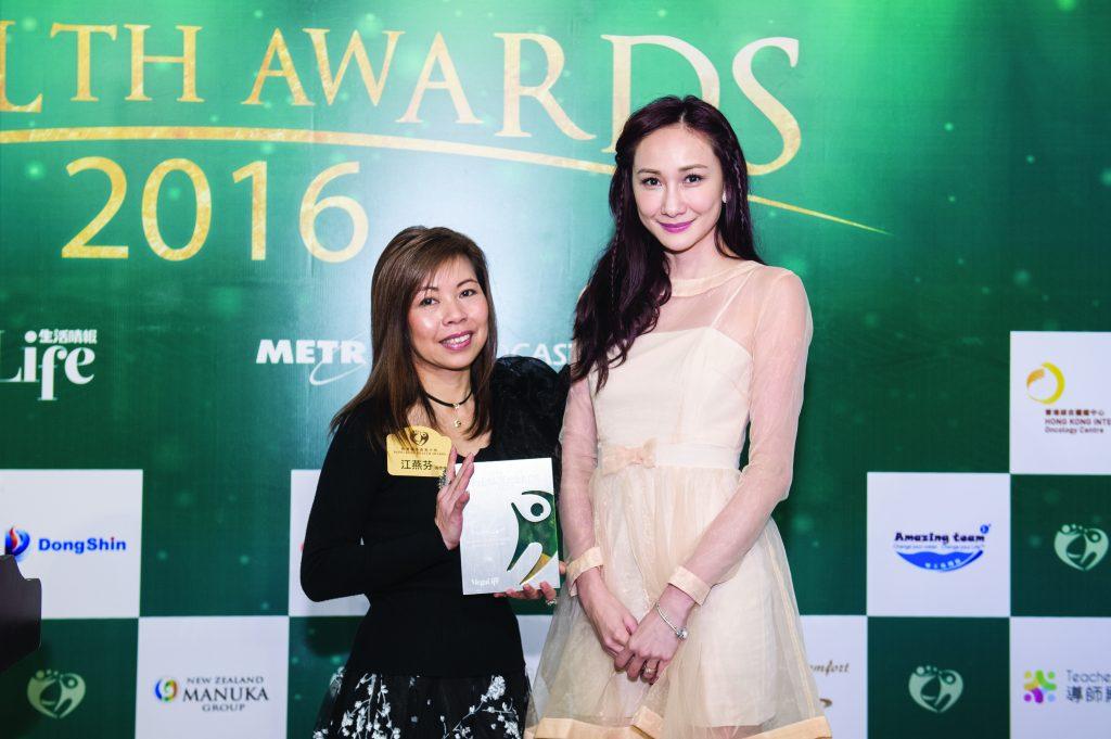 Bewellopment思立敏公司創辦人江燕芬女士(左)在著名模特兒何紫綸小姐手上接過獎座。