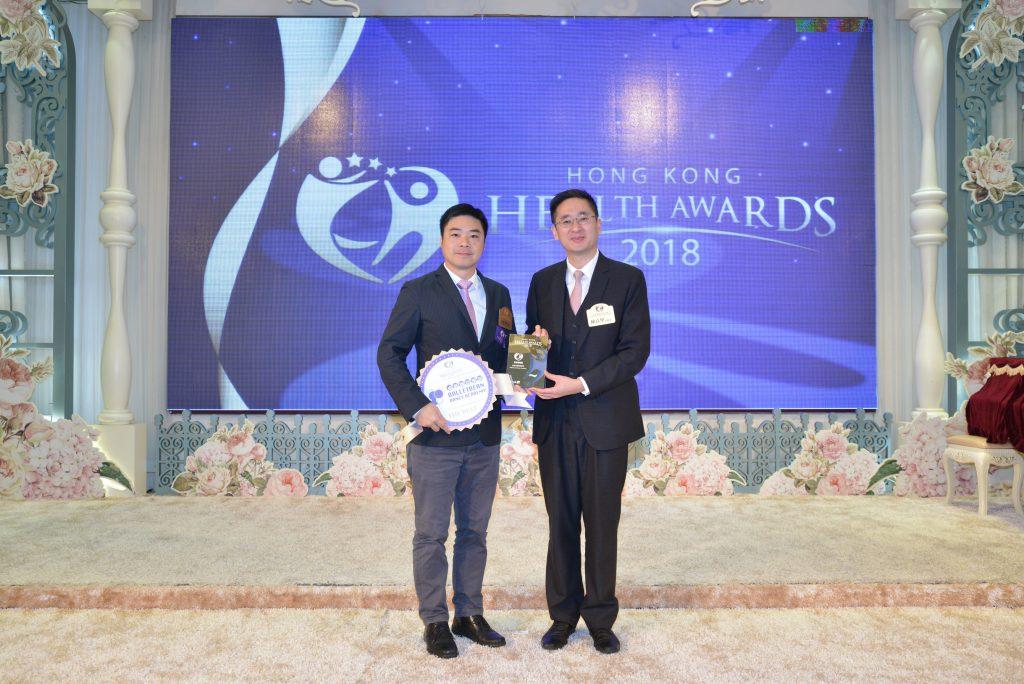 卓藝舞蹈學院行政總監何家亮先生(左)從商務及經濟發展局副局長陳百里博士手上接過獎座。