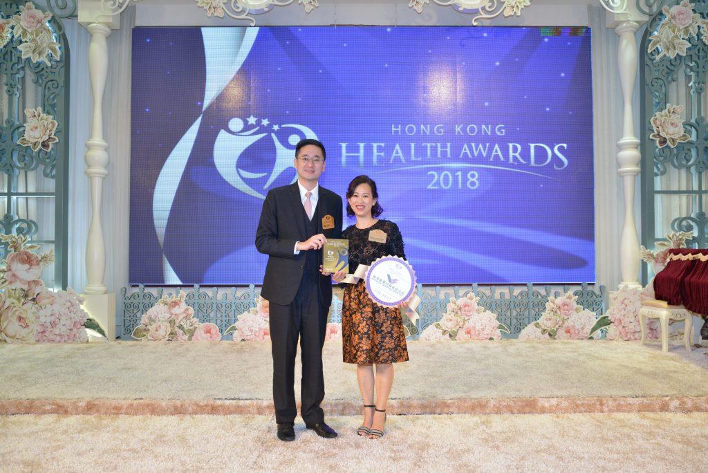 Shirley Price代理韻濤集團董事總經理Sidney Chang(右) 在商務及經濟發展局副局長陳百里博士手中接過獎座。