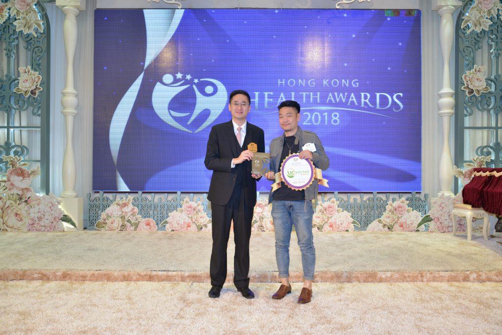 UG Kitchen代表Kevin Chan(右)由商務及經濟發展局副局長陳百里博士頒發獎座。
