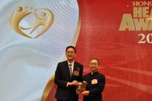 領袖人物獎得主骨科及運動醫學權威容樹恆醫生(右)從商務及經濟發展局副局長陳百里博士接過獎座。